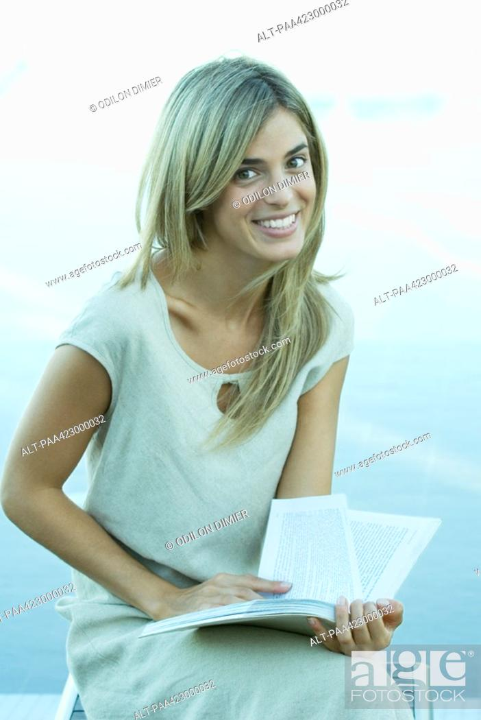 Stock Photo: Young woman holding open book, smiling at camera.