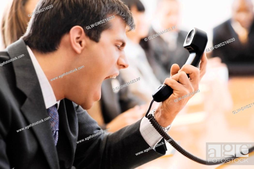 Stock Photo: Close-up of a businessman shouting in front of a telephone receiver.