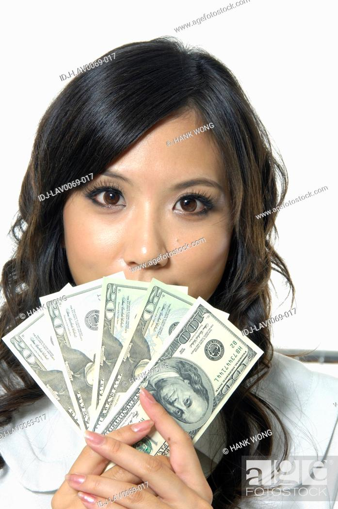 Stock Photo: Woman with dollar bills in front of her face.