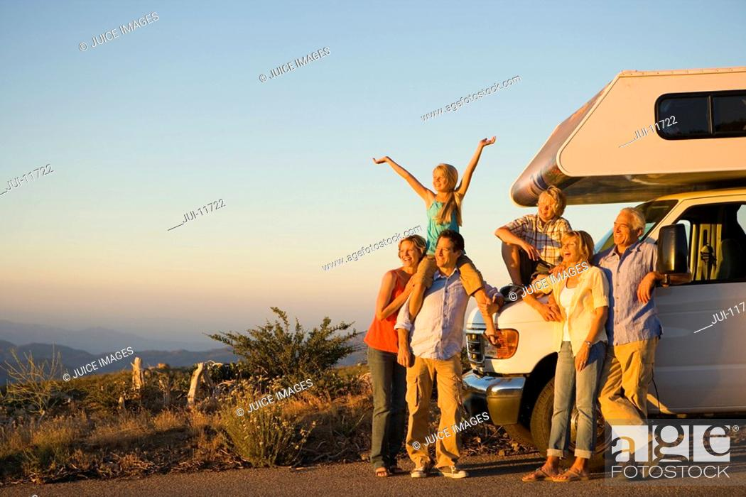 Stock Photo: Three generations of family by motor home on side of road at dusk, smiling.