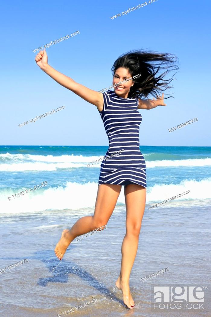 Stock Photo: Beautiful summer brunette girl jumping on the blue beach.