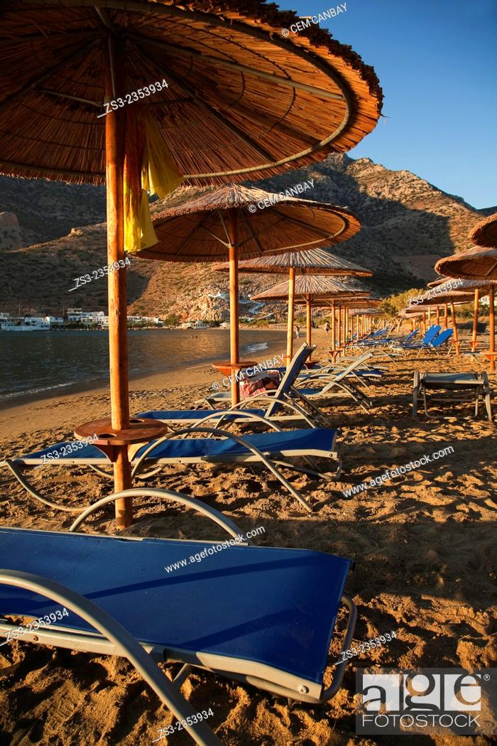 Stock Photo: Thatched umbrellas on the beach near the port in Kamares at sunset, Sifnos, Cyclades Islands, Greek Islands, Greece, Europe.