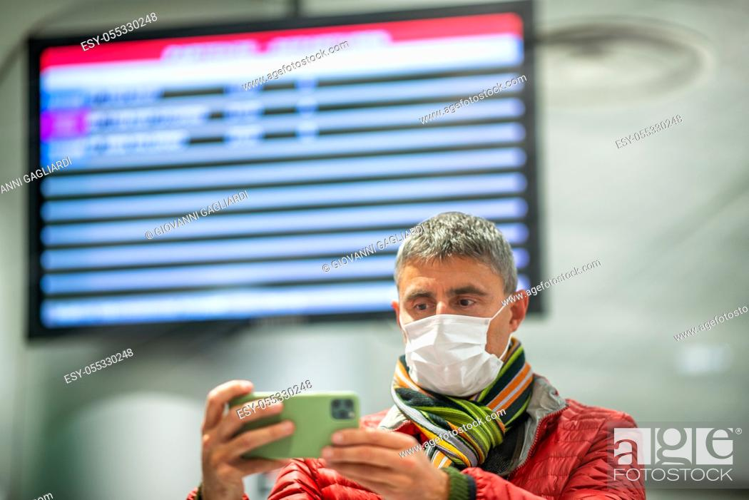 Photo de stock: Man wearing face mask at the airport in front of departure board.