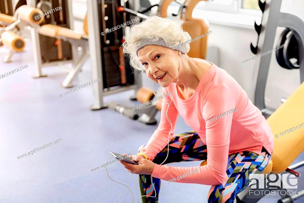Stock Photo: Portrait of beaming grandmother hearing song. She sitting on bench in fitness center.