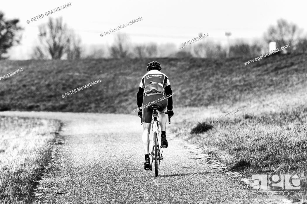 Stock Photo: Bath - the Netherlands - A cyclist riding along the Westerschelde on a bike.