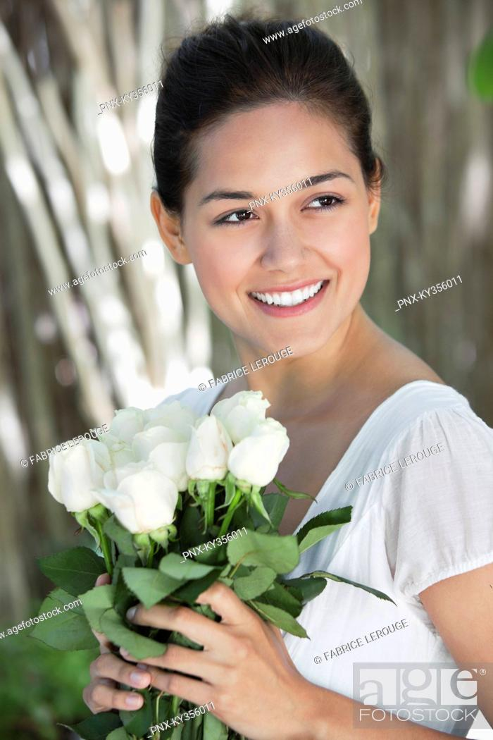 Stock Photo: Young woman holding bunch of white flowers and smiling.