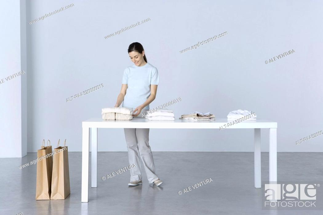 Stock Photo: Woman standing at table, looking at folded sweater.