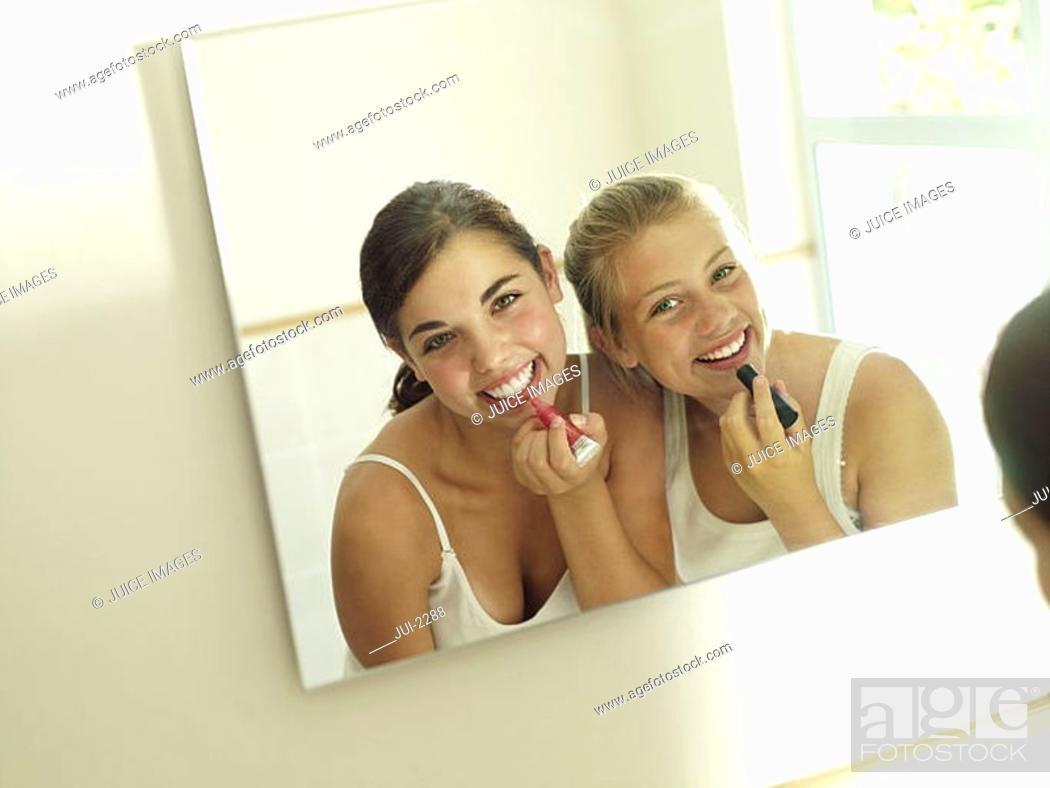 Stock Photo: Teenage girls 15-17 applying make-up, reflection in mirror, smiling, rear view, portrait tilt.