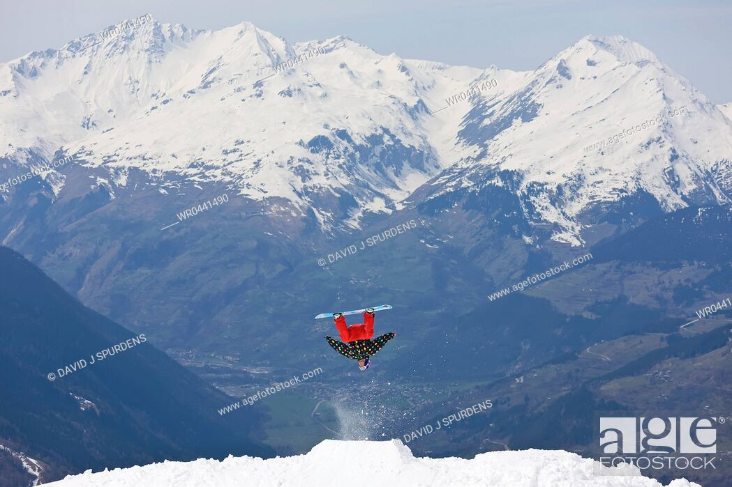 Stock Photo: A snowboarder doing a big back flip of a snowy mountain.
