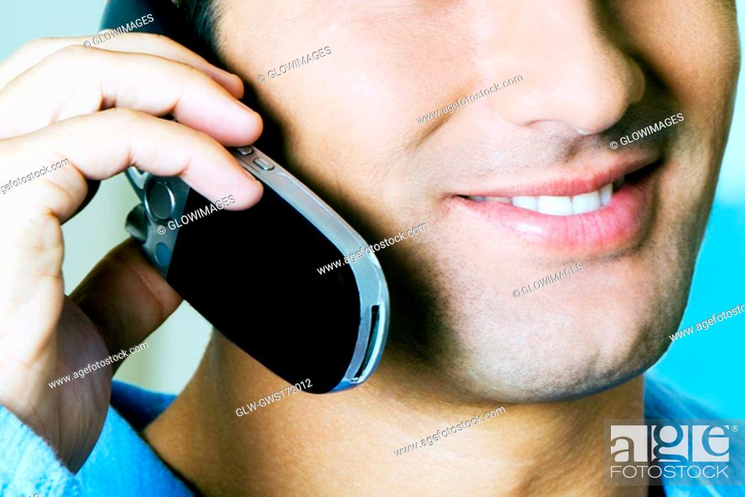 Stock Photo: Close-up of a young man using a mobile phone.