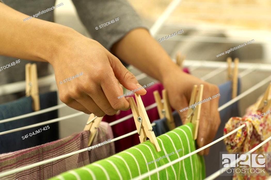 Stock Photo: Woman hanging washing on clothes horse.