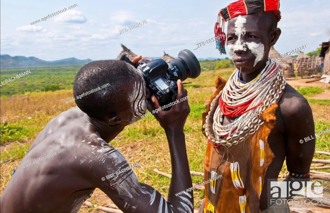 Stock Photo: Korcho Ethiopia Africa village Lower Omo Valley Karo tribe with painted faces with boy using modern camera taking photos 25.
