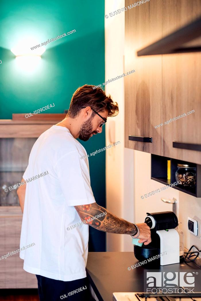 Stock Photo: Mid adult man pouring coffee from coffee machine on kitchen counter.