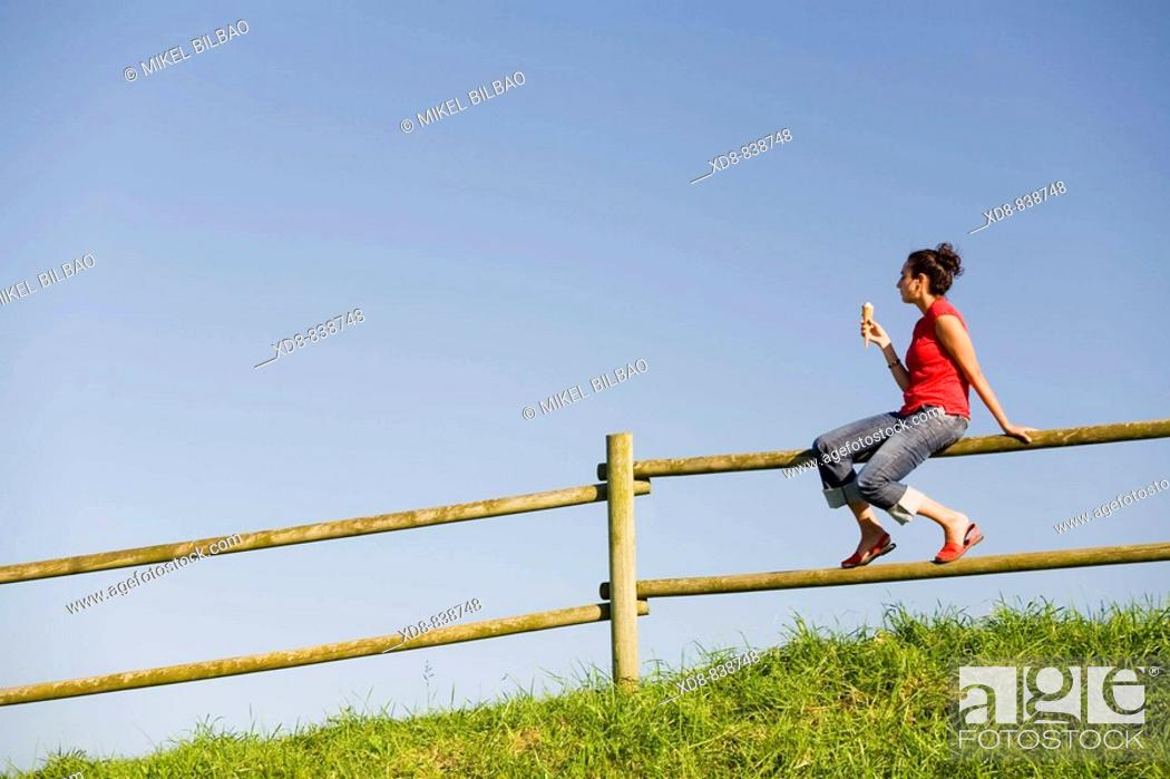 Stock Photo: Portrait of a young woman sitting on a fence eating a ice cream.