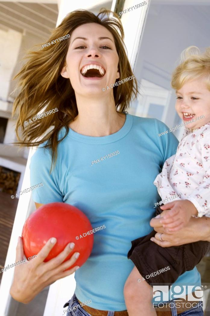 Stock Photo: Smiling woman carrying little girl.