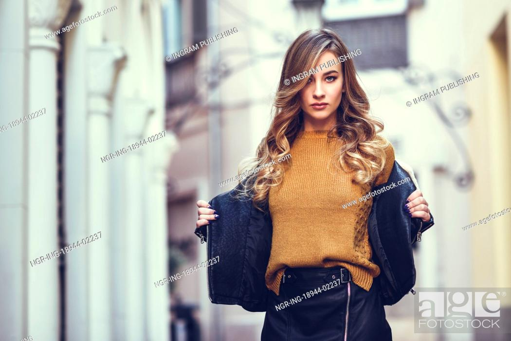 e58929e16 Stock Photo - Blonde woman in urban background. Beautiful young girl wearing  black leather jacket and mini skirt standing in the street.