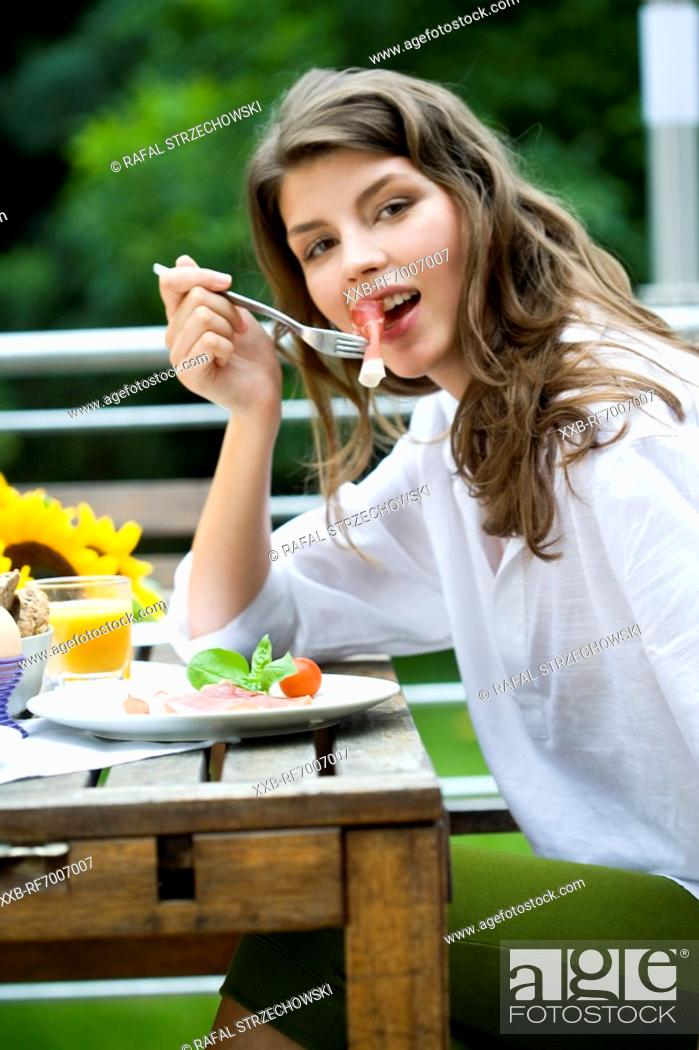 Stock Photo: Woman eating on the terrace.