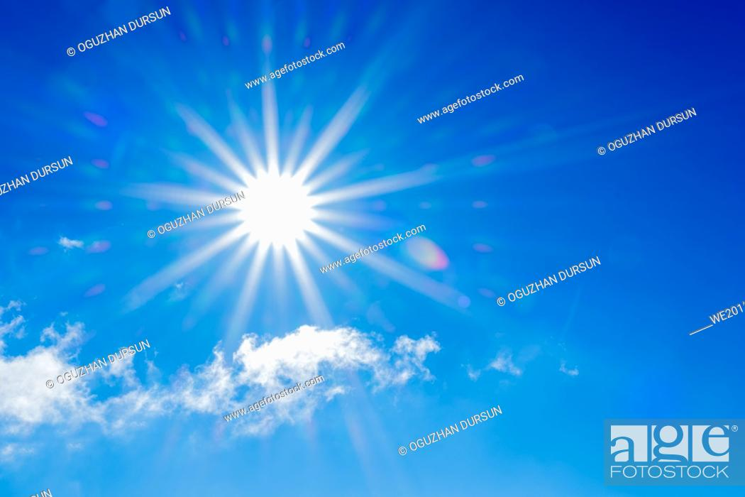 Stock Photo: Sunlight and flares on blue sky and clouds around in winter time.