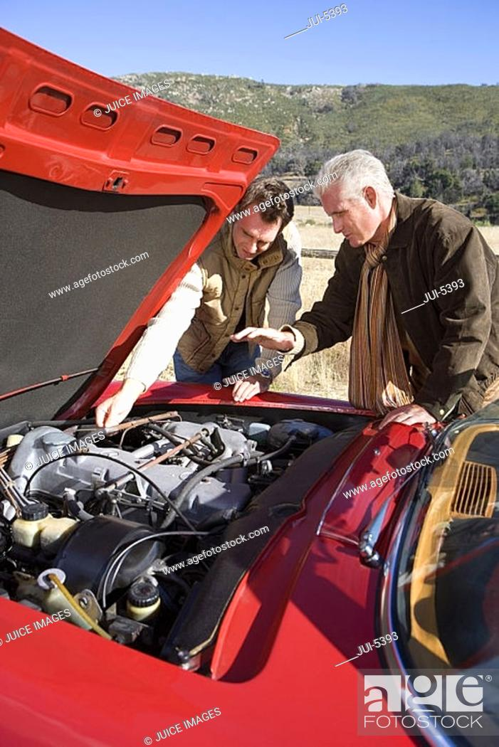 Stock Photo: Senior man and adult son experiencing car trouble on country road, looking at engine, side view.