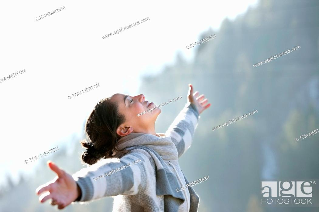 Stock Photo: Woman with head back and arms outstretched.