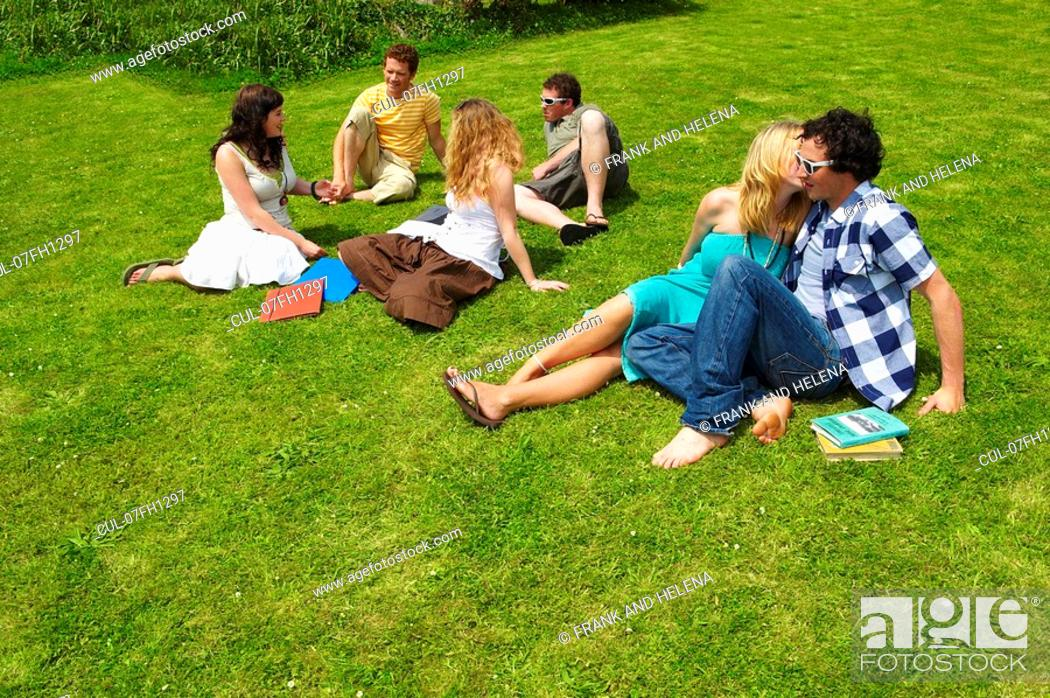 Stock Photo: Group of young people sitting on lawn.