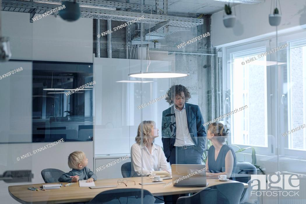 Stock Photo: Business team with a boy having a meeting in office.