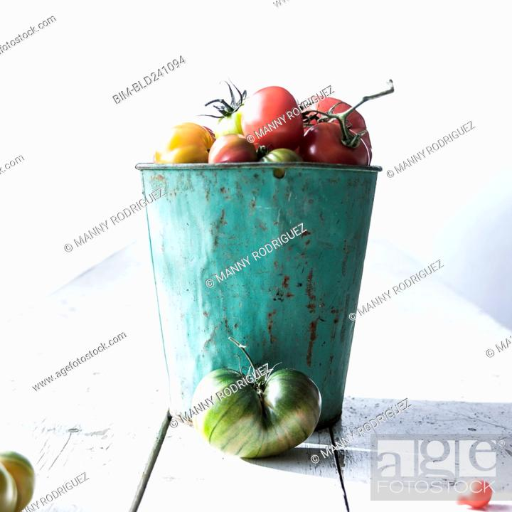 Photo de stock: Bucket of fresh tomatoes on wooden table.