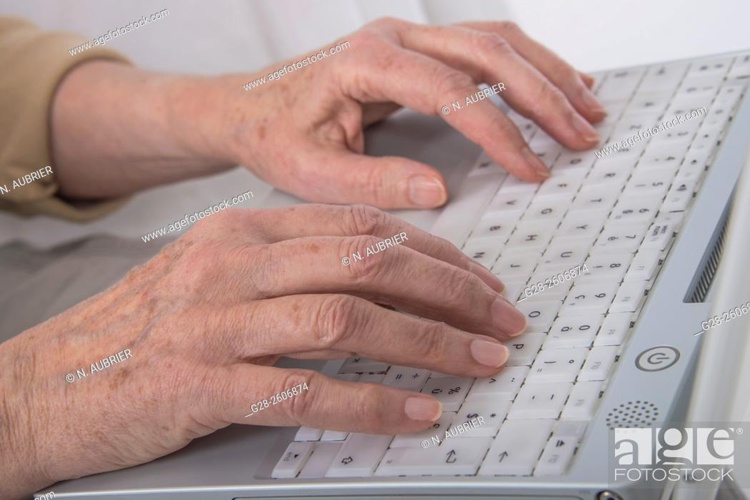 Stock Photo: Senior Woman 's hands typing on a white computer keyboard.