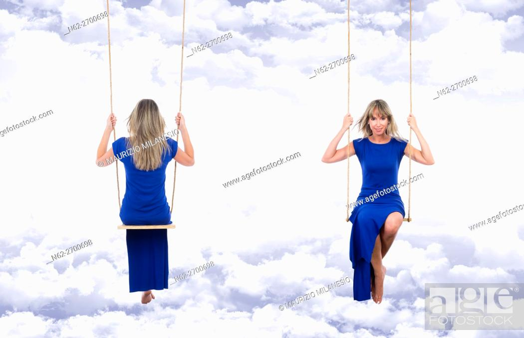 Stock Photo: Smiling and relaxed blonde woman, front and back view, wearing a long blue dress on the swing, suspended through the clouds of a fantasy blue sky.
