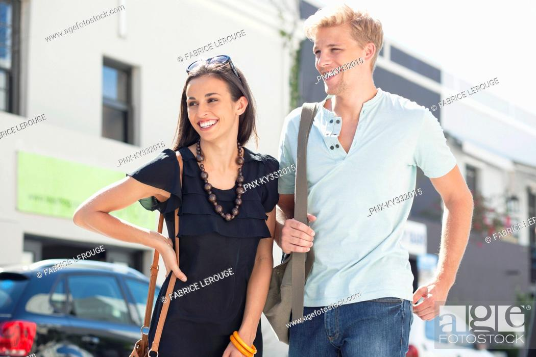 Stock Photo: Smiling young couple standing on a street.