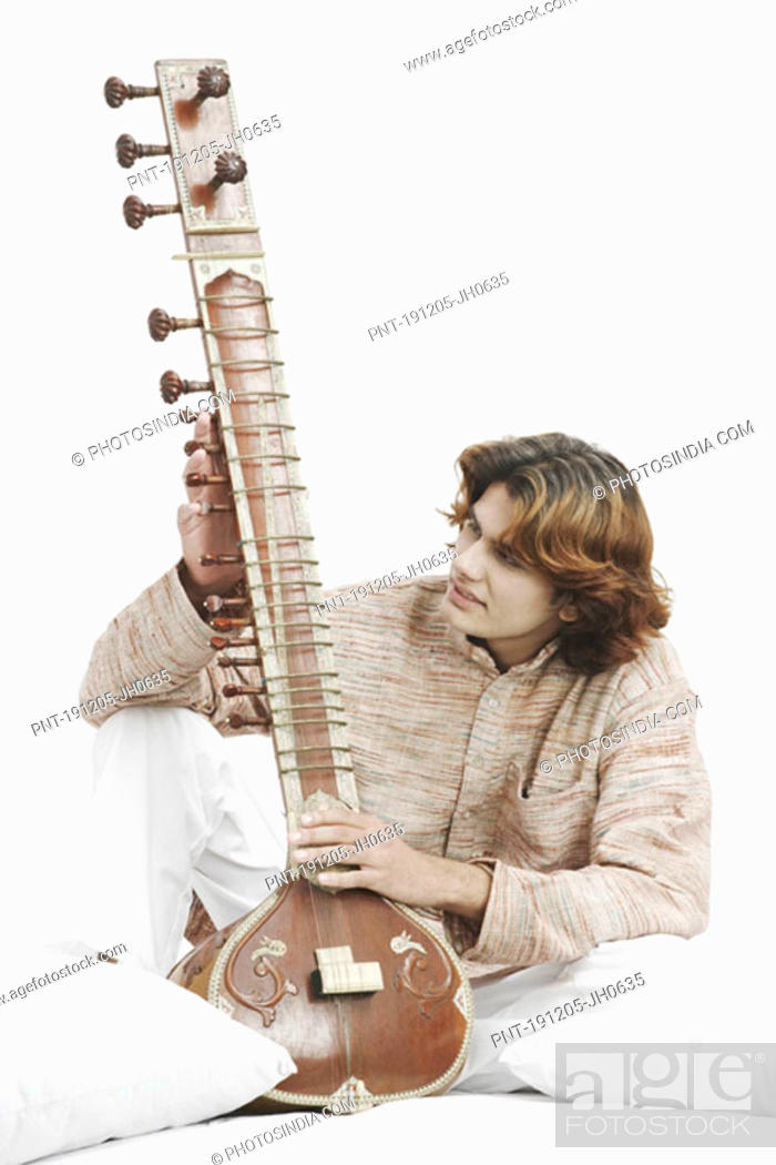 Stock Photo: Close-up of a male musician looking at a sitar.