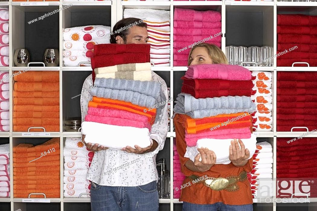 Stock Photo: Couple shopping in department store, holding two large piles of towels beside shelf, faces obscured.