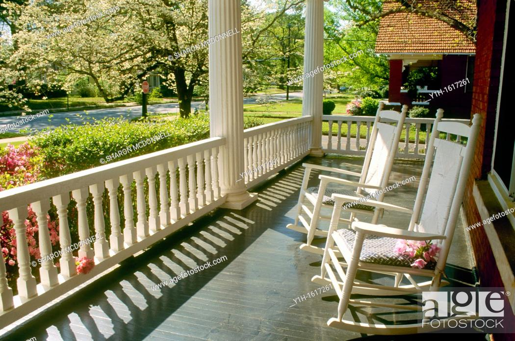 Stock Photo: Two rocking chairs sit on wide front porch looking out over spring street blooming with dogwood, azaleas, and pears, Georgia, USA.