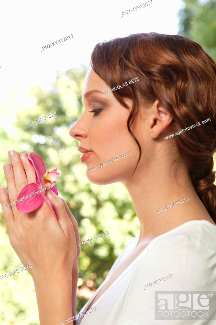 Stock Photo: Young woman holding orchid.