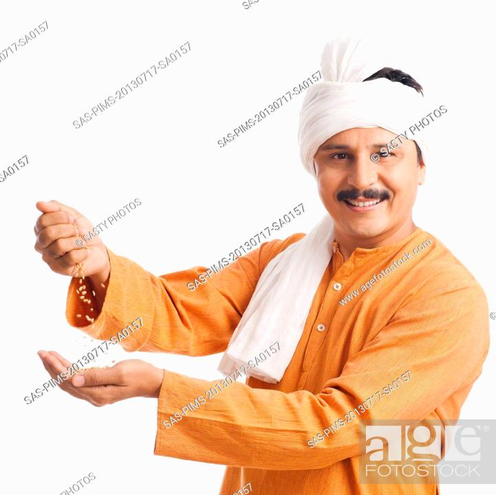 Stock Photo: Portrait of a farmer holding wheat in his hand and smiling.