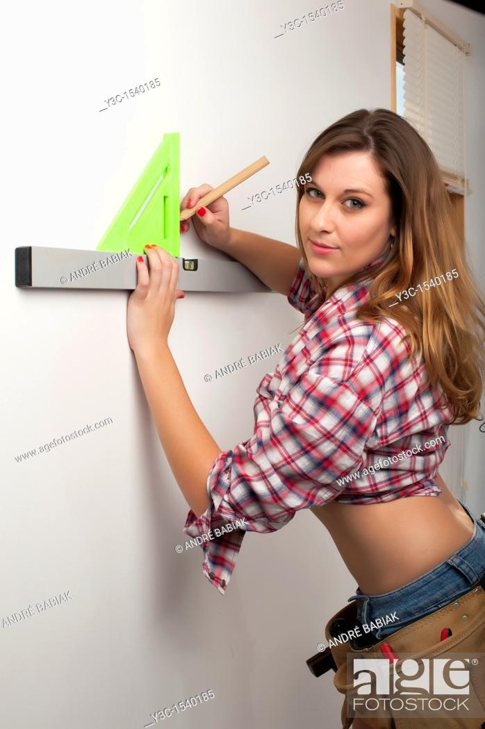 Stock Photo: Female Handyman working with level and angle.