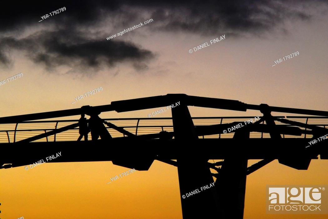Stock Photo: Silhouette of the Millenium Bridge and two pedestrians seen against a Winter sunset in London, England.