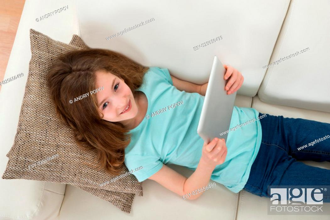 Stock Photo: High Angle View Of Girl Lying On Sofa Using Digital Tablet In Living Room.