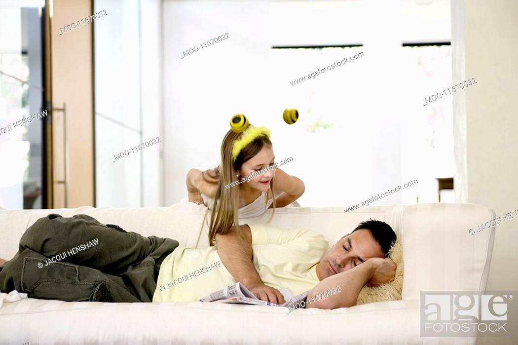 Stock Photo: Man napping on sofa with daughter leaning over.