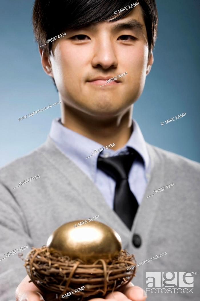 Stock Photo: man holding a golden egg in a nest.