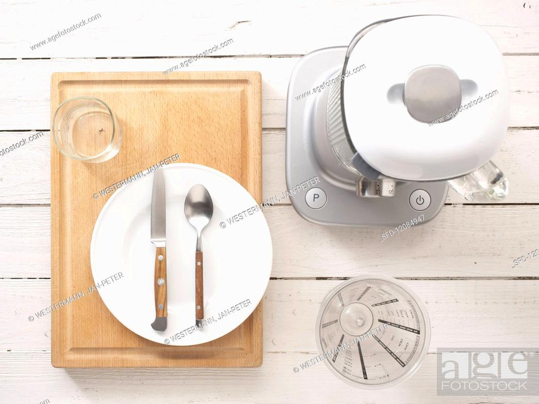 Stock Photo: Kitchen utensils: a blender, measuring cup, cutlery and a plate.