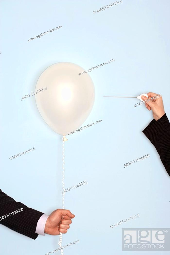 Stock Photo: Businessmen holding and popping balloon close-up of hands.