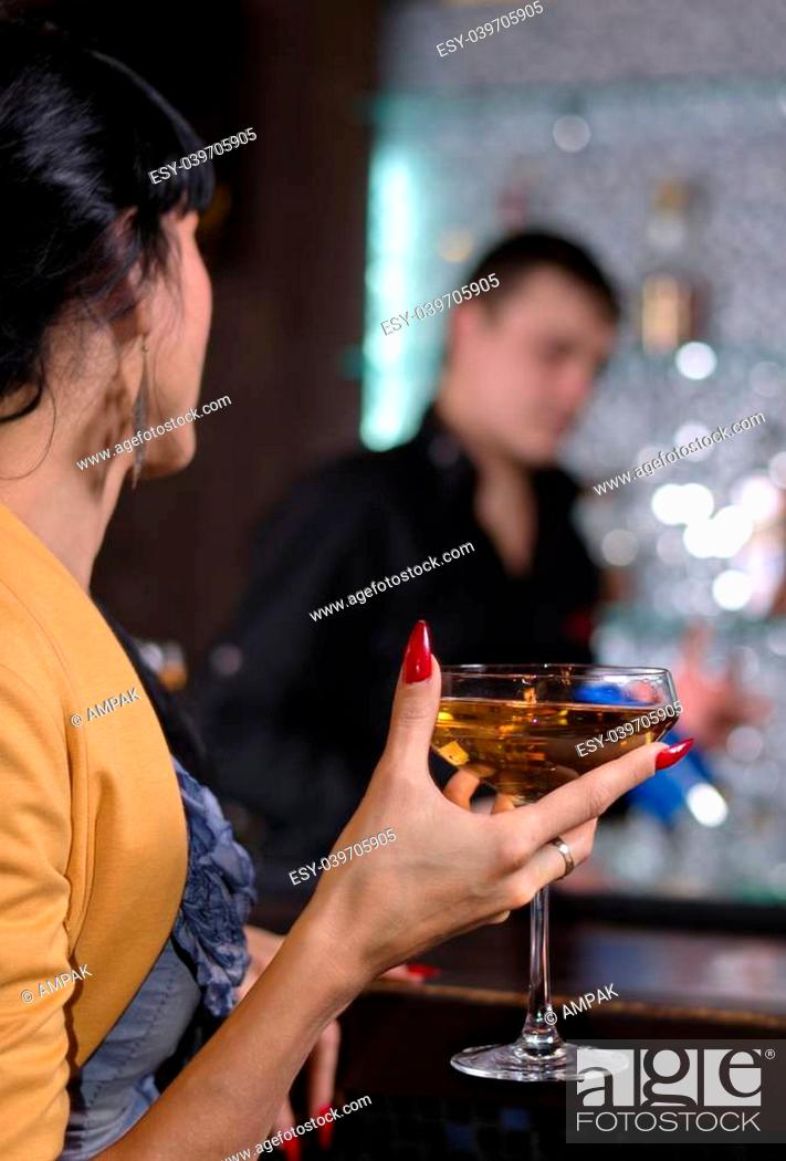 Stock Photo: Elegant woman drinking a martini cocktail with closeup view of her hand with beautifully manicured red painted nails holding the glass.