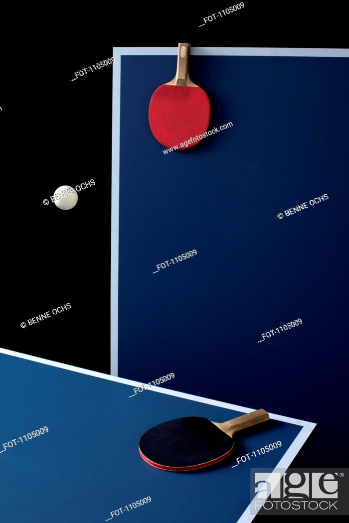 Stock Photo: Table tennis tables, bats and a ball mid-air.