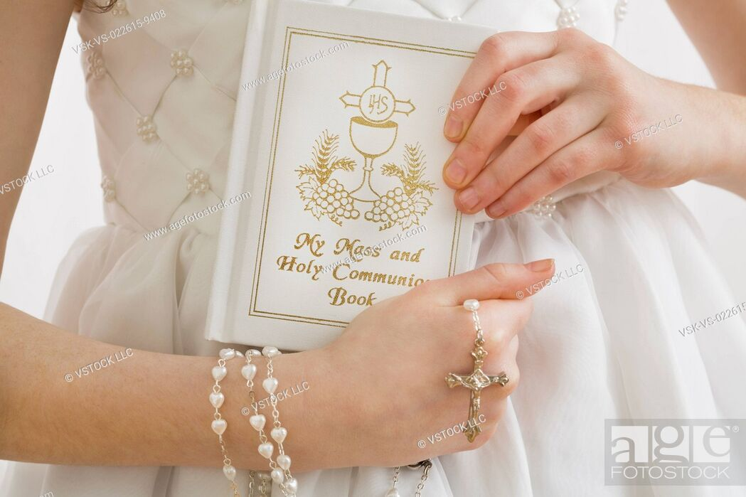 Stock Photo: Mid-section of girl (8-9) holding rosary beads and book.