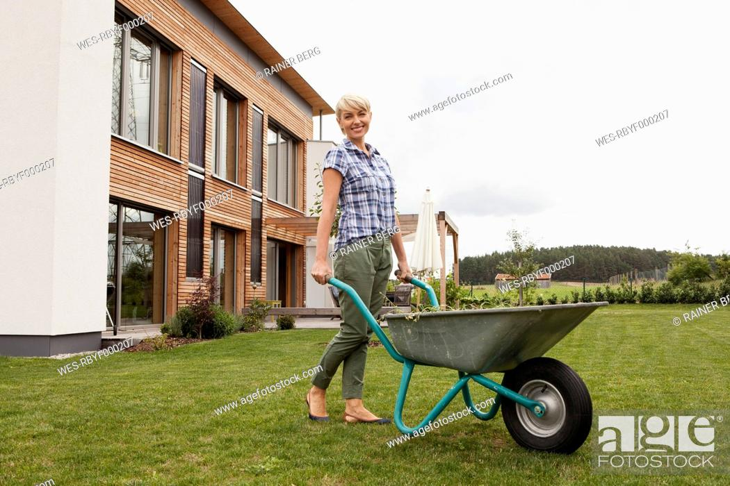 Stock Photo: Germany, Bavaria, Nuremberg, Mature woman with wheelbarrow in garden.