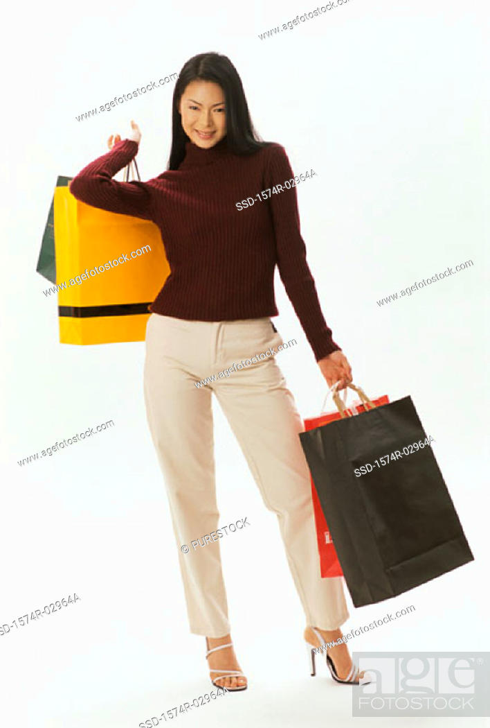 Stock Photo: Portrait of a young woman carrying shopping bags.