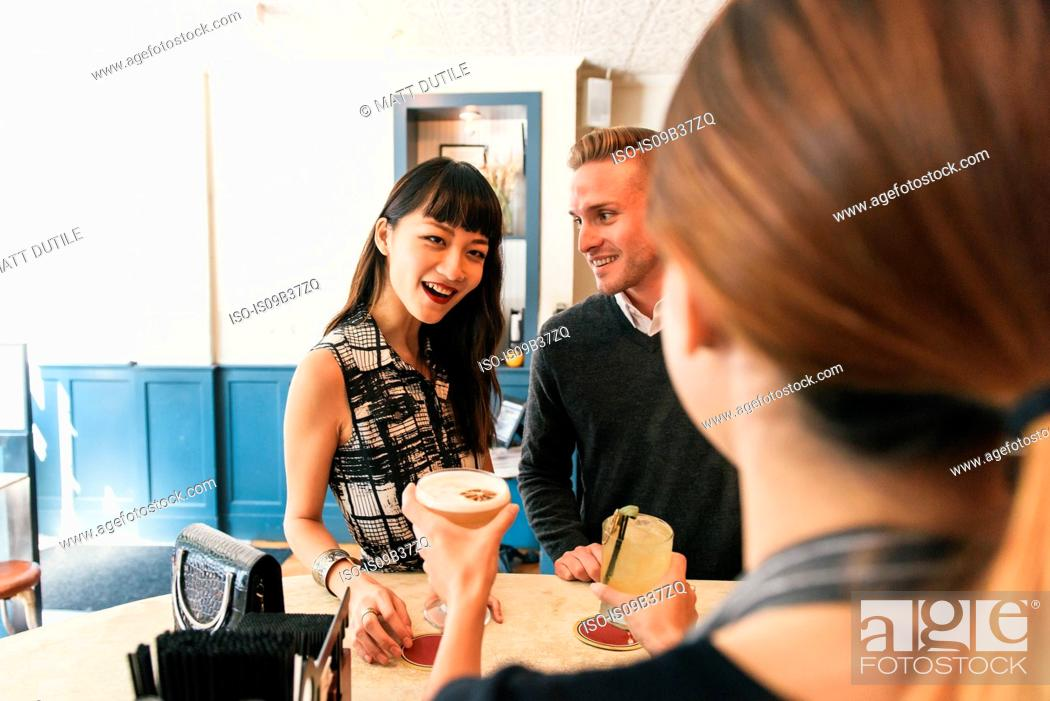 Stock Photo: Young couple in bar, bring served drinks by bar worker.