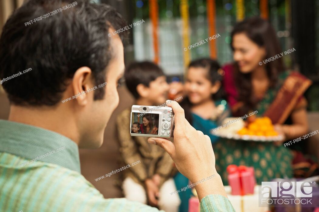 Stock Photo: Man taking a picture of his family with a camera on Diwali.