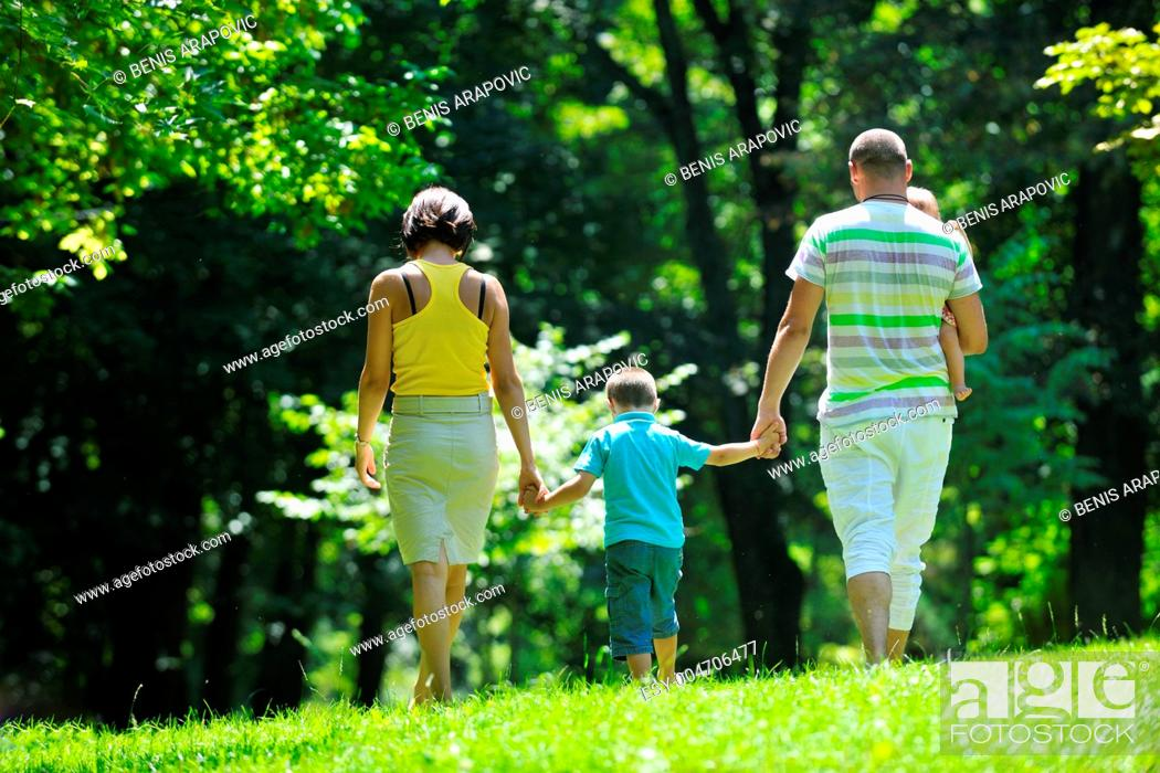 Stock Photo: happy young couple with their children have fun at park.